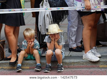 STOCKHOLM SWEDEN - JUL 30 2016: Two young boys looking boored when waiting for the Pride parade in the Pride parade July 30 2016 in Stockholm Sweden