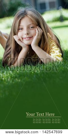 portrait of little girl laying on the grass in summer environment. banner