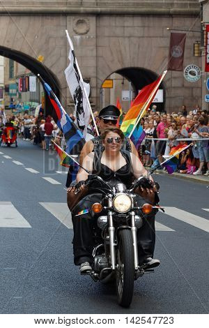 STOCKHOLM SWEDEN - JUL 30 2016: Two woman dressed in leather clothes on a motorcycle decorated with pride flags in the Pride parade July 30 2016 in Stockholm Sweden