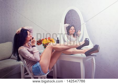 beautiful young lady at mirror admires reflexion in the bedroom