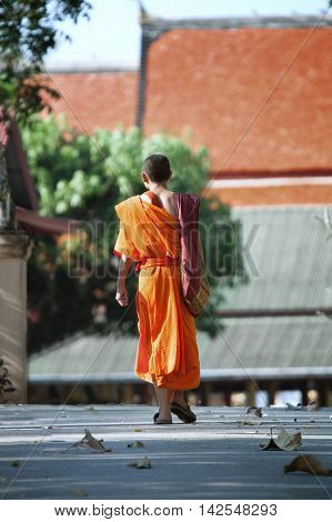 Photo of thai Buddhist monk is going toward to temple