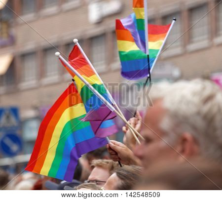 STOCKHOLM SWEDEN - JUL 30 2016: Hands waiving the colorful rainbow pride flag in the Pride parade July 30 2016 in Stockholm Sweden
