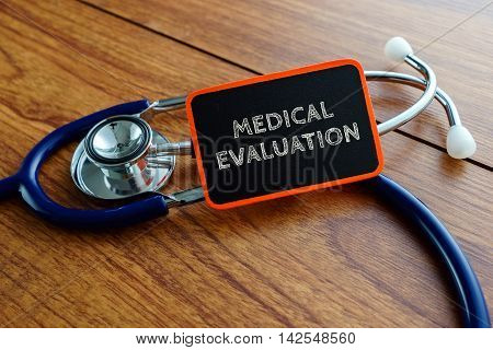 Medical Concept.word Medical Evaluation With Stethoscope On Wooden Table.
