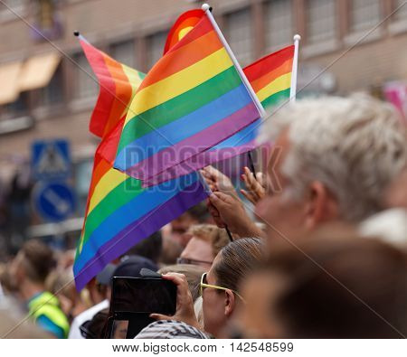STOCKHOLM SWEDEN - JUL 30 2016: Hands waiving the colorful rainbow pride flag people watching in the Pride parade July 30 2016 in Stockholm Sweden