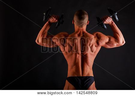Bodybuilder with relief muscular body and dumbbells