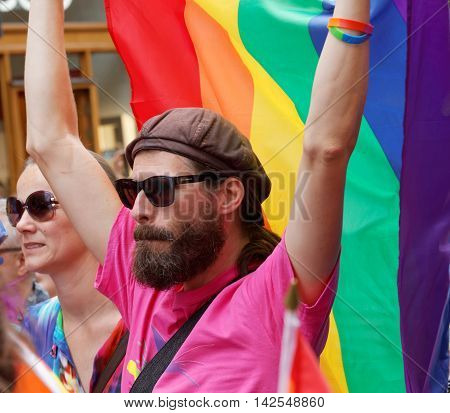 STOCKHOLM SWEDEN - JUL 30 2016: Man with beard wearing glasses holdin the rainbow Pride flag in the Pride parade July 30 2016 in Stockholm Sweden