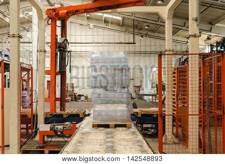 ISTANBUL, TURKEY- OCTOBER 15, 2012: Packaging line robotic arm covering water bottles with nylon