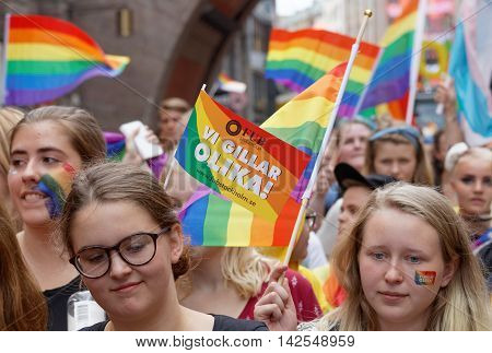STOCKHOLM SWEDEN - JUL 30 2016: Girls and boys waiving the rainbow Pride flags in the Pride parade July 30 2016 in Stockholm Sweden