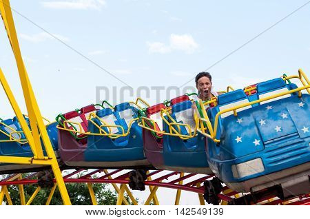 Happy teenager in amusement park rides down