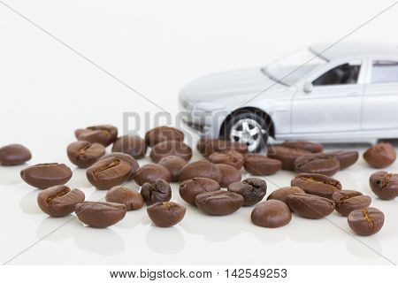 horizontal photo of coffee beans with a car on the background.