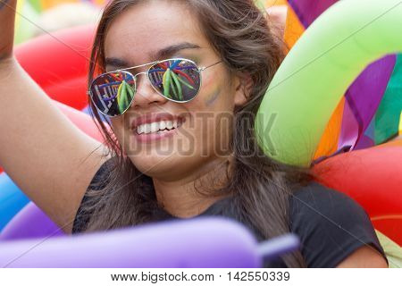 STOCKHOLM SWEDEN - JUL 30 2016: Beautiful smiling latin girl wearing sunglasses reflecting colorful balloons in the Pride parade in the Pride parade July 30 2016 in Stockholm Sweden