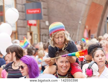 STOCKHOLM SWEDEN - JUL 30 2016: Blonde little boy wearing a rainbow hat fixing the rainbow flag sitting on his mothers shoulders in the Pride parade July 30 2016 in Stockholm Sweden