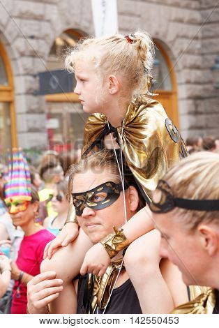STOCKHOLM SWEDEN - JUL 30 2016: Blonde little girl wearing a golden jacket sitting on her mothers shoulders in the Pride parade July 30 2016 in Stockholm Sweden