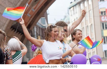 STOCKHOLM SWEDEN - JUL 30 2016: Dancing and singing girls and boys waiving the rainbow pride flag in the Pride parade July 30 2016 in Stockholm Sweden