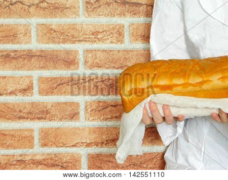 Warm and fresh bread in the baker`s hands. Baker is standing in front of the red brick wall.