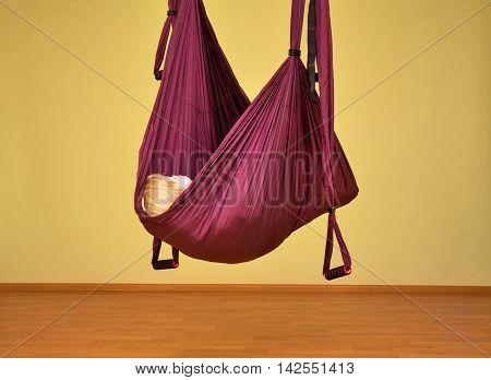 Little girl making aerial yoga exercises indoor aerial yoga