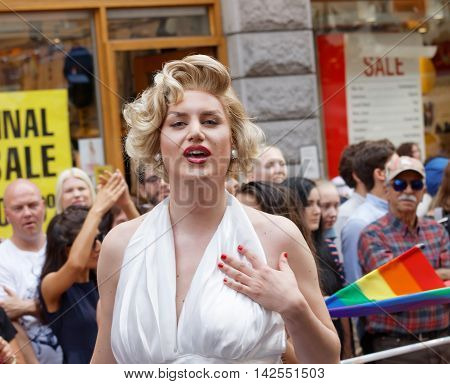 STOCKHOLM SWEDEN - JUL 30 2016: Transvestite man dressed as Marilyn Monroe wearing a white dress in the Pride parade July 30 2016 in Stockholm Sweden