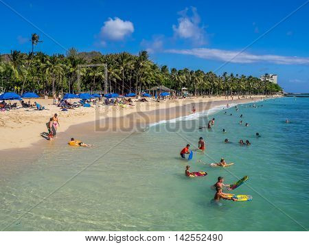 HONOLULU, USA - AUG 4: Sun lovers on Waikiki beach on August 4, 2016 in Honolulu, Usa. Waikiki beach is neighborhood of Honolulu, best known for white sand and surfing.