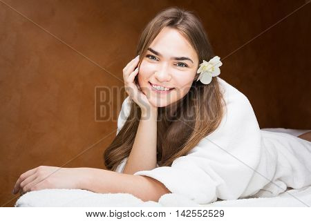 Smiling attractive young brunette woman in a white robe