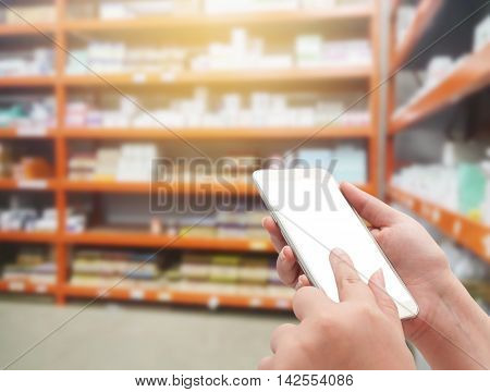 Hand with smartphone white screen on blurred in pharmacy store background