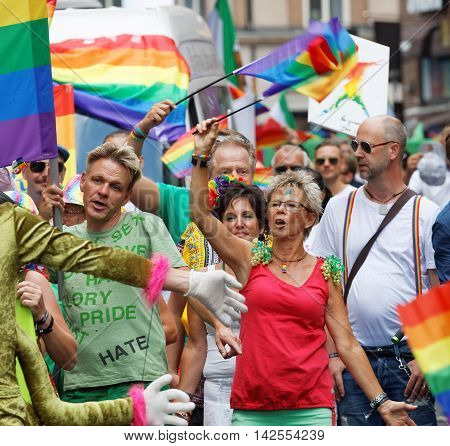 STOCKHOLM SWEDEN - JUL 30 2016: Senior woman and men waiving the rainbow Pride Parade flag in the Pride parade July 30 2016 in Stockholm Sweden