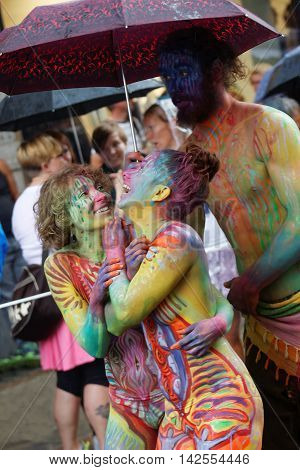 STOCKHOLM SWEDEN - JUL 30 2016: Colorful body painted girls laughing a boy holding an umbrella in the Pride parade July 30 2016 in Stockholm Sweden