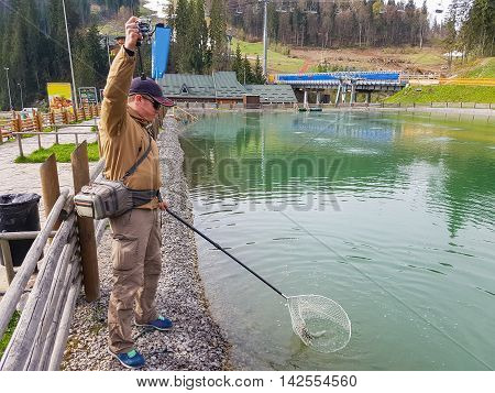 Trout fishing in the pond. AREA fishing. Fisherman catches a trout in the lake