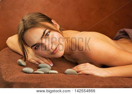 Beautiful brunette woman with spa stones indoor