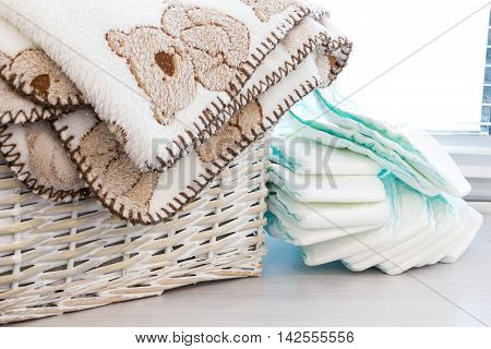 grey basket with children's toys diapers accessories on table on grey wooden background. Mother care. children's room pile of blue clothes for newborn boy