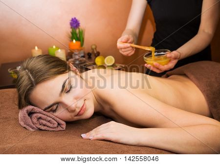 Beautiful woman in spa salon having spa therapy honey procedure with hands of masseur