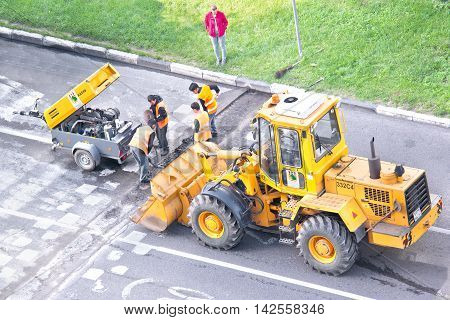 MOSCOW RUSSIA - August 14.2016: Brigade of workers of municipal service repairs a transition across the motor-car road