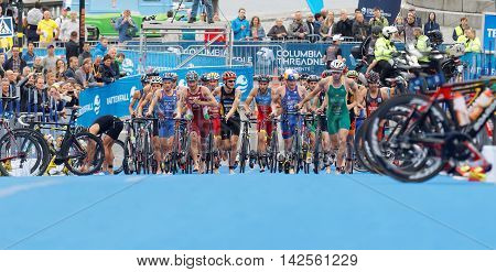 STOCKHOLM - JUL 02 2016: Large group of running triathletes running with bicyles in the transition zone in the Men's ITU World Triathlon series event July 02 2016 in Stockholm Sweden