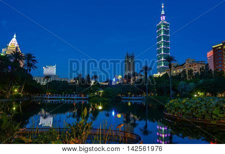 Taipei city skyline and night lighting reflecting in a peaceful lake after sunset