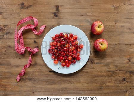 Diet concept. cherries on plate red apples and measuring tape on wooden table