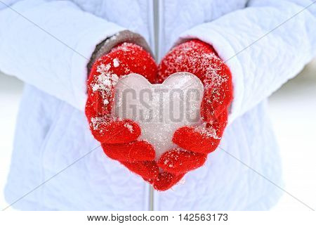 Girl wearing white winter coat and holding ice heart in red gloves.