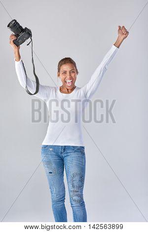 Happy overjoyed woman holding dslr camera, celebrating