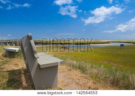 Concrete bench near the walkway to the dunes. Wooden walkway extends over marshland toward the distant dunes and ocean In Sandwich Cape Cod Massachusetts USA