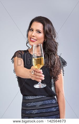 Pretty glamorous woman holding a glass of champagne for a toast, cheers to the camera lens