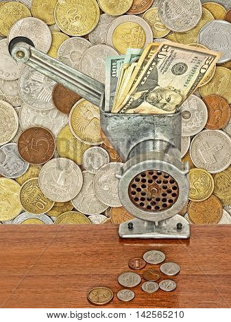 Dollar banknotes in meat grinder and coins on table on lot of different coins background.Money and busines concept.