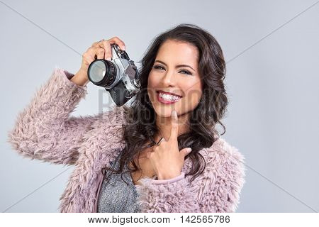 Young beautiful woman in glamoros party clothes holding a vintage retro camera, taking photos