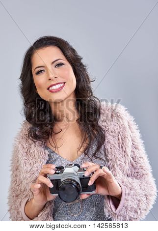 Young beautiful woman in glamourous party clothes holding a vintage retro camera, taking photos