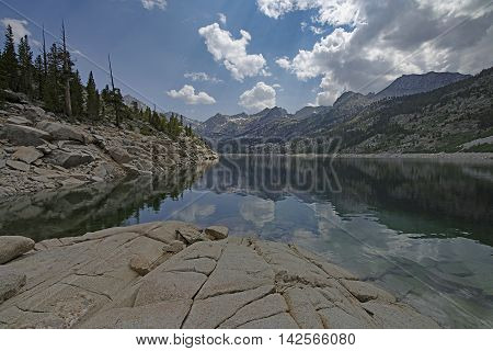 Mountain lake with reflections of the encompassing mountains.  Dramatic clouds approach in a blue sky. Granite rocks lead into the water.  South Lake near Bishop, California.