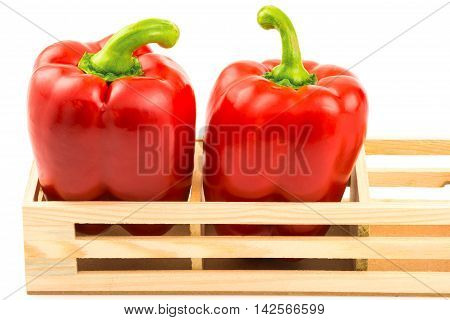 Macro view of group of sweet red peppers in the wooden box