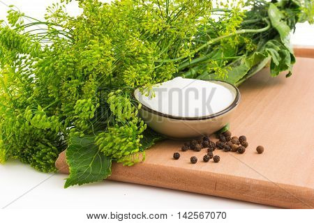 Macro view of bloom dill with black pepper on the wooden cutting board