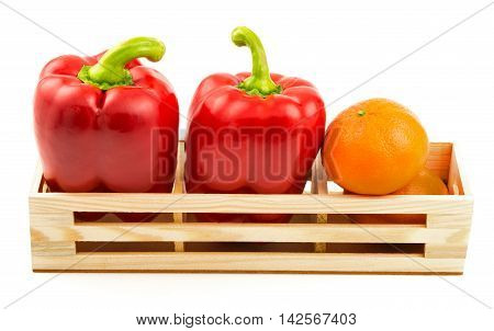 Group of sweet red peppers and ripe tangerine in the wooden box