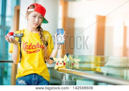 BANGKOK THAILAND – August 142016: Trainer girl playing pokemon pokemon ball and Pokemon Go mobile game app on smart phone gadget with play screen catching cartoon in real world using gps technology Lighting with sun flare