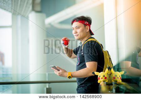 BANGKOK THAILAND – August 142016: Trainer boy playing pokemon pokemon ball and mobile pokemon go game app on smart phone gadget Lighting with sun flare