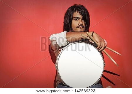 young drummer holding sticks and snare isolated on red background looking into the camera