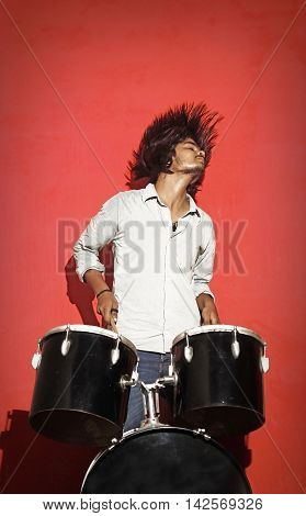 young drummer head banging isolated on red background