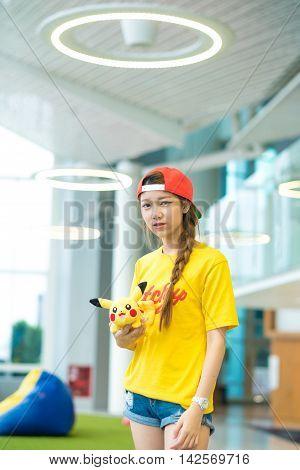 BANGKOK THAILAND – August 142016: Trainer girl playing pokemon pokemon ball Lighting with sun flare
